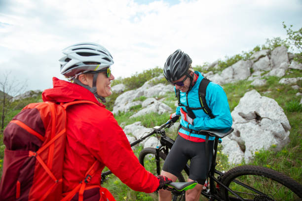 Mountain biking Male and female bikers are having a ride in the mountains. georgijevic mountain biker stock pictures, royalty-free photos & images