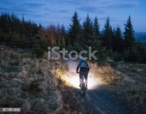 Rear view of a man using bright lights to illuminate the mountain bike trail in front of him as daylight fades.