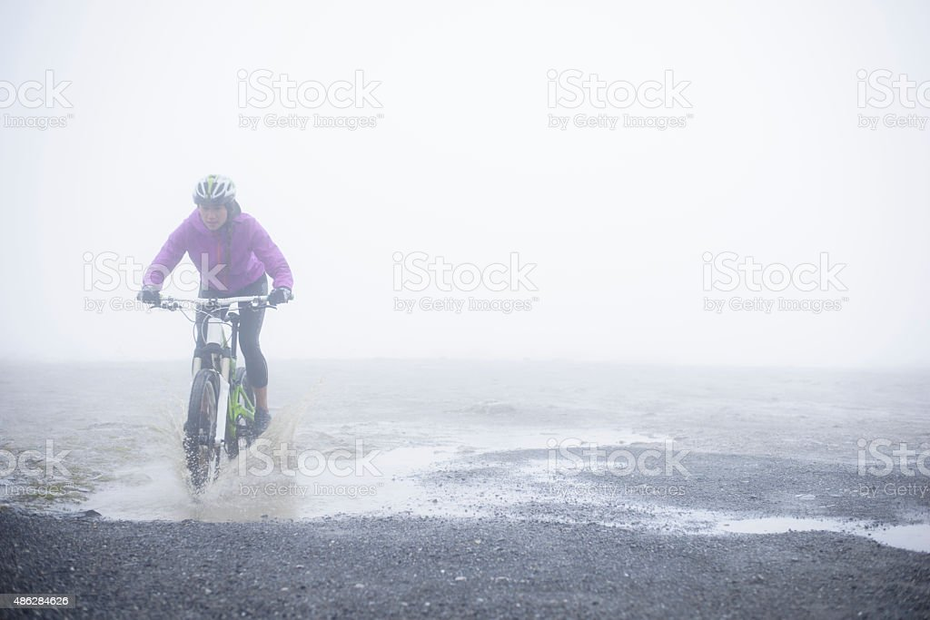 Mountain Biking - Woman Rider Splashing Through a Puddle royalty-free stock photo
