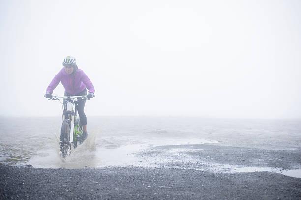VTT-femme cycliste dans une flaque d'eau - Photo