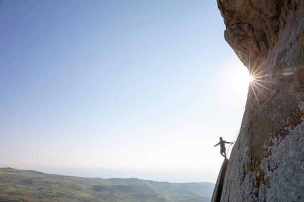 Mountain climber ascends rock face at sunrise stock photo