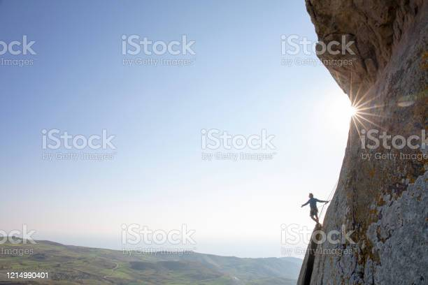 Photo of Mountain climber ascends rock face at sunrise
