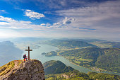Mountain Climber at Summit Cross on top of Mount Schafberg, Alps