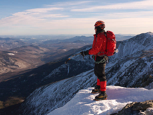 Mountain climber enjoying panoramic view Ice climber enjoying the view atop Mount Washington in New Hampshire after climbing a gully in Hungtington Ravine mount washington new hampshire stock pictures, royalty-free photos & images