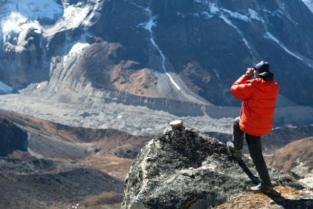 暖かいジャケットの登山家は谷の写真を撮る - ダウンジャケット ストックフォトと画像