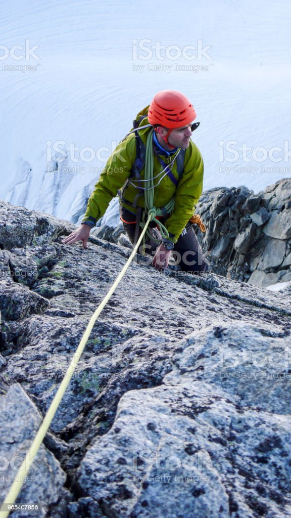 mountain climber on a rock climbing route high above a wild and torn glacier below zbiór zdjęć royalty-free