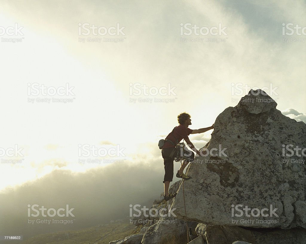 A mountain climber reaching the top of a mountain stock photo