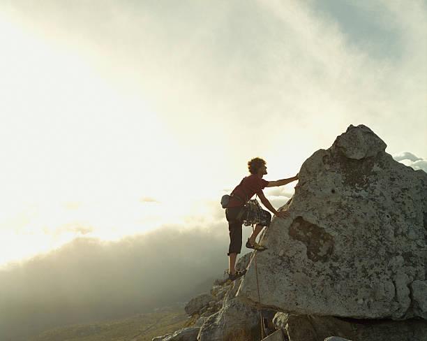 un alpiniste atteint le sommet d'une montagne - escalade photos et images de collection