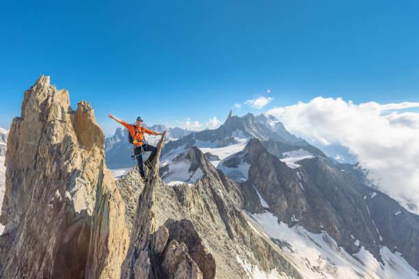 Bergsteiger sitzt auf scharfen Felsen pinnacle – Foto