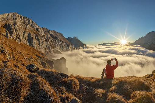 istock Mountain Climber take picture with mobile Phone at sunrise - Alps 1070159552