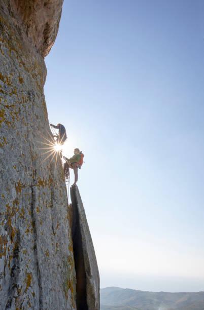 Mountain climbers ascend rock face at sunrise stock photo