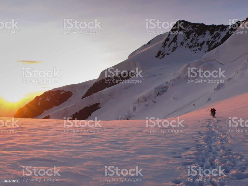 mountain climbers cross a glacier high up in the Alps at dawn and sunrise stock photo