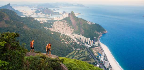 Mountain climbers hiking above Rio De Janeiro Brazil stock photo