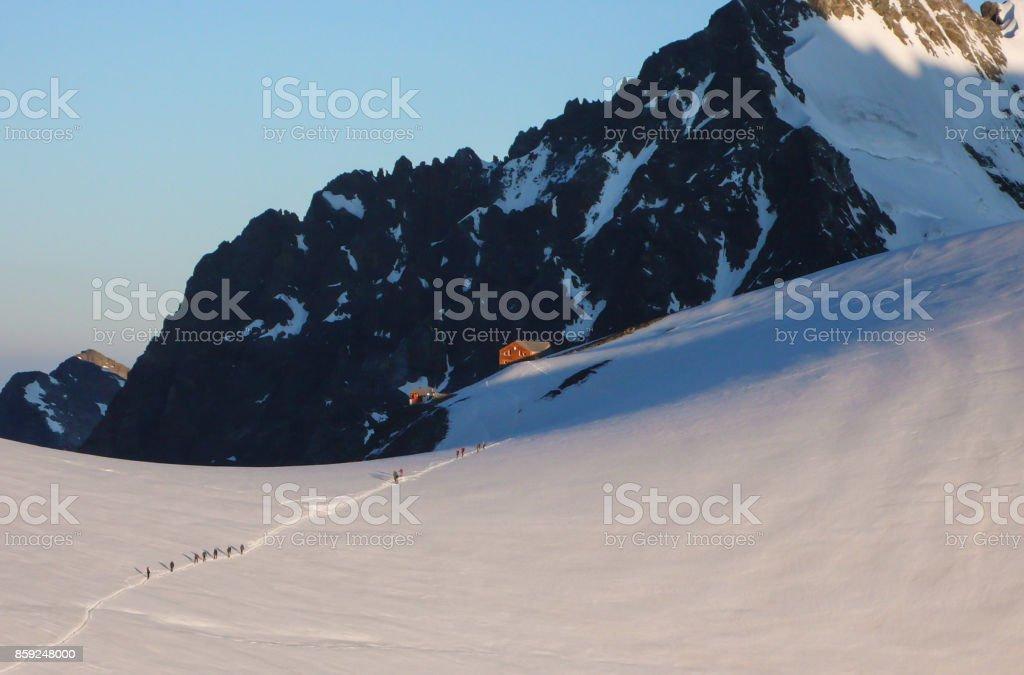 mountain climbers leaving hut at dawn stock photo