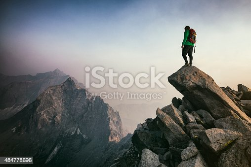 Strong mountain climber looking into distance during a sunset as clouds roll in