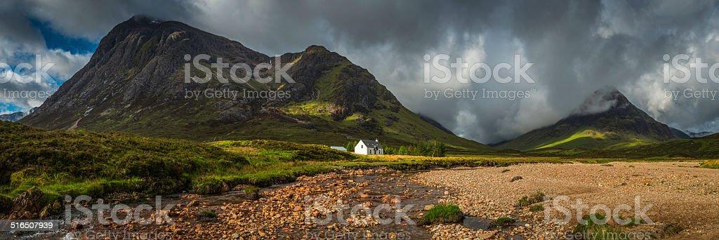 Mountain cottage below dramatic wilderness peaks panorama Glencoe Highlands Scotland stock photo