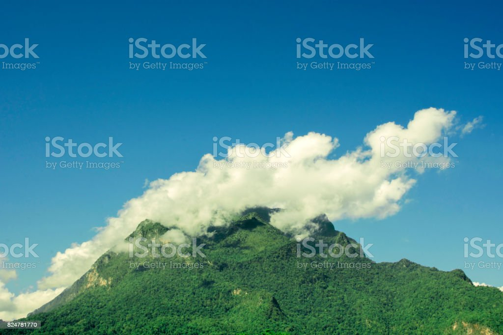 Mountain covered with clouds and fogs on top of mountain stock photo