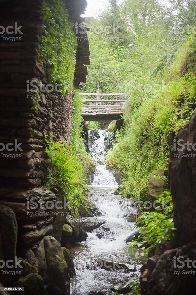 Mountain creek, bridge, house wall. stock photo