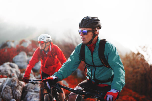 Mountain cycling Male and female bikers are having a ride in the mountains. georgijevic mountain biker stock pictures, royalty-free photos & images