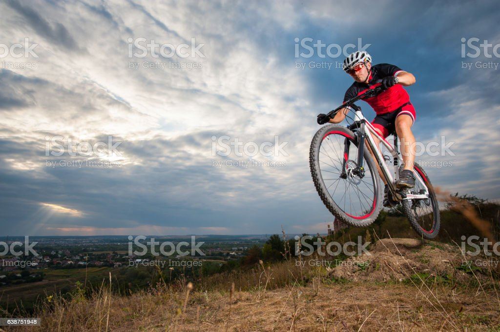 Mountain cyclist riding donwhill against blue evening sky stock photo