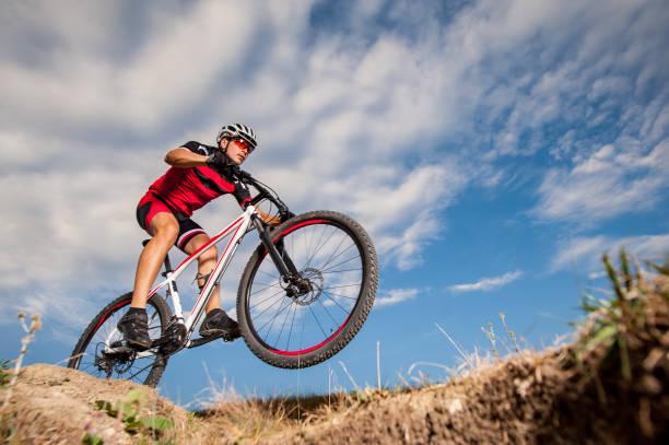 mountain cyclist riding donwhill against blue evening sky - casque de protection au sport photos et images de collection