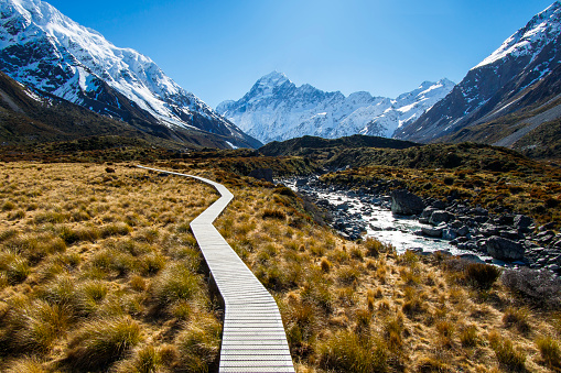 Mountain footpath boardwalk in valley surrounded by snowcapped mountains with no people on the way to Mount cook, New Zealand