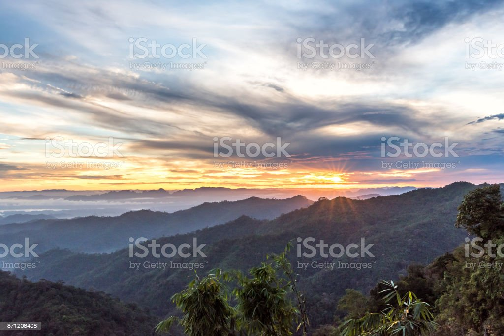 Mountain forest landscape under sunrise sky with clouds. stock photo