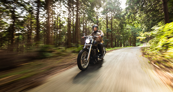 September/29/2020 at Gozaisho mountain forest road a man is riding his Harley Davidson motorbike. The trees and road have motion blur due to the slow shutter speed used.