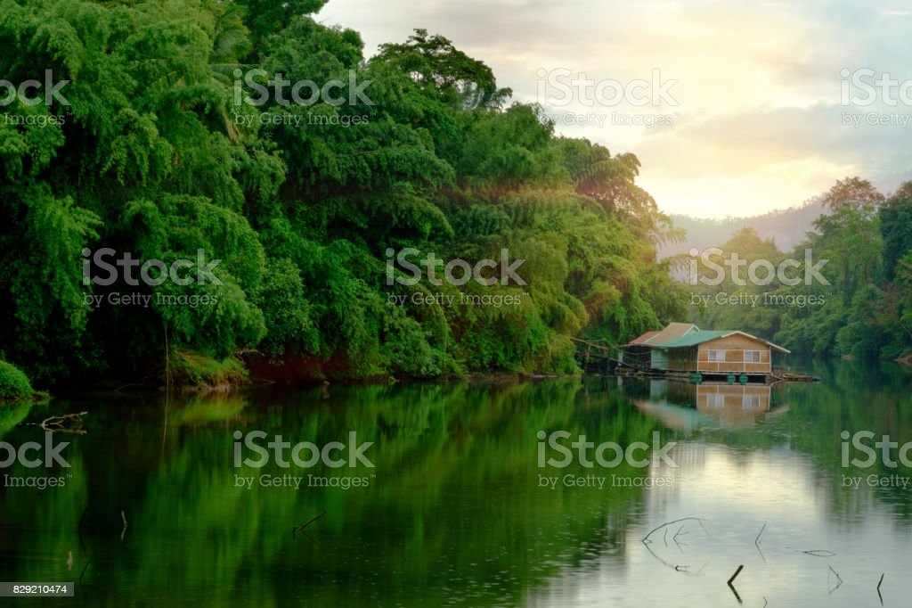 Mountain forest with fog and houseboat on kwai river landscape on rain in kanchanaburi, Thailand. Natural concept stock photo