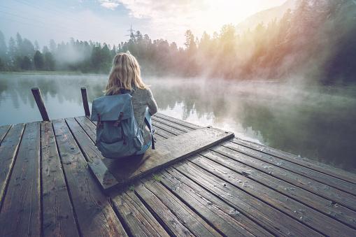 Mountain girl enjoying morning fog from lake pier, sun rising