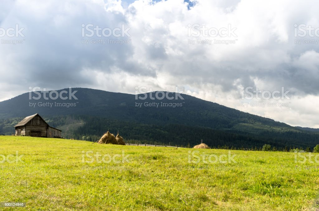 Mountain glade with a house from a log house and sheaves of hay. stock photo