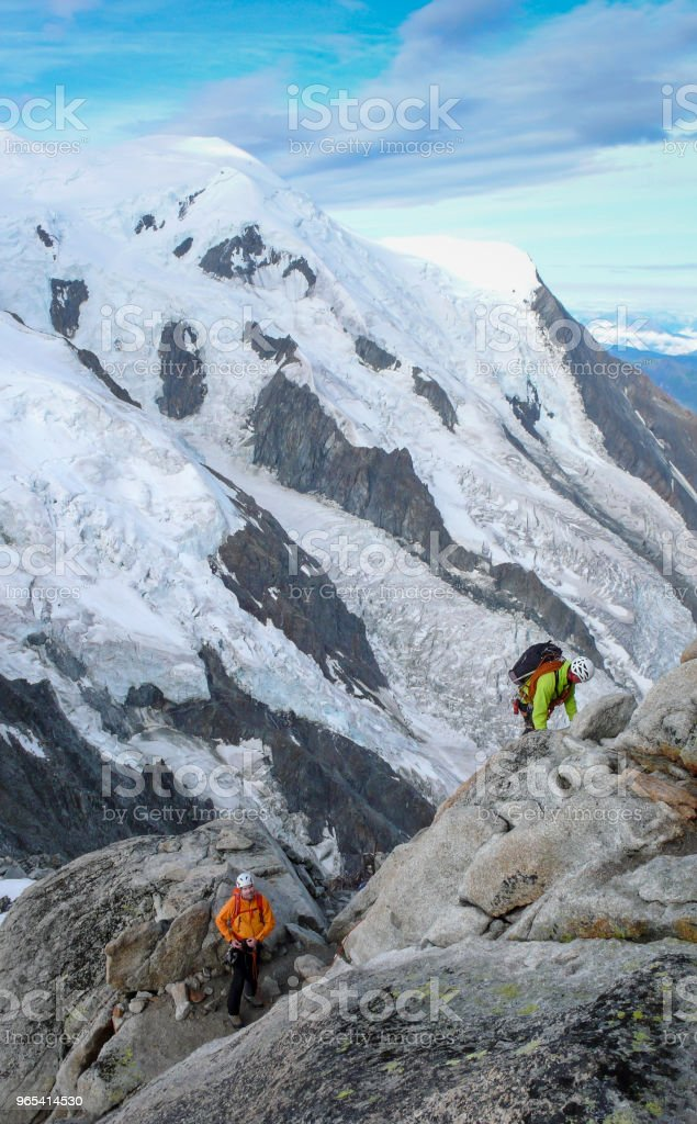 mountain guide and a male client on a rocky ridge heading towards a high summit in the French Alps near Chamonix royalty-free stock photo