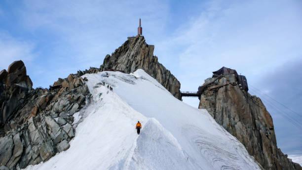 guide de montagne et un client masculin sur un cap de crête de neige vers le bas d'un sommet de haut - Photo