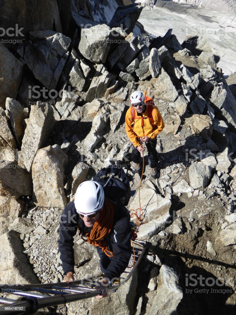 mountain guide and client get ready to climb a ladder to the exit of their climbing route in Chamonix near Mont Blanc royalty-free stock photo