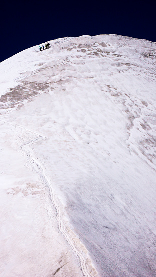 istock mountain guide descending from the summit over a steep glacier with his clients 951001678