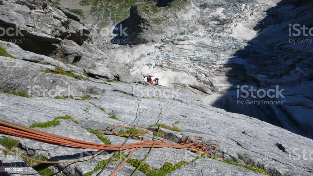 mountain guide on a hard granite climb to a high alpine peak in the Swiss Alps stock photo