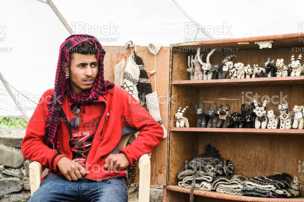 Mountain guide seating by a shelf full of local crafts for sell in a canteen tent along the Markha valley hike stock photo
