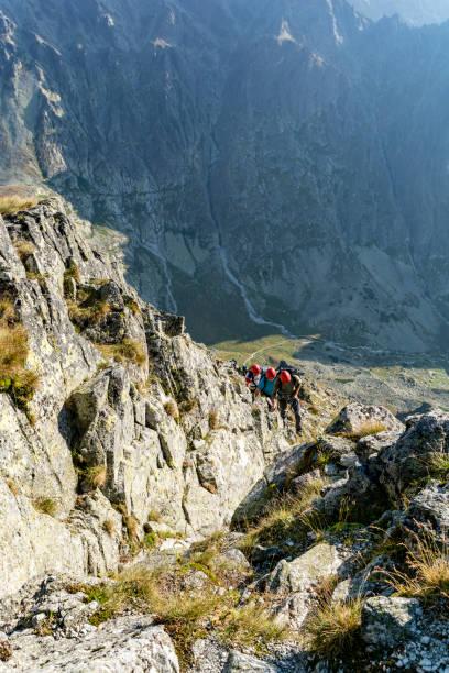 Kayalık arazide önde gelen ve dağlarda müşterilerinin (turistlerin) ipi belaying Dağ kılavuzları. stok fotoğrafı