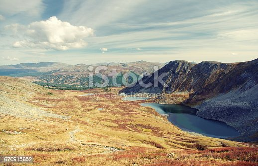 istock Mountain highland yellow valley with lakes on the background of the ridges under blue sky and white clouds Altai Siberia Russia 670915652