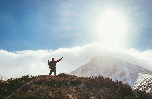 Mountain hiker greeting the sun in Highland stock photo