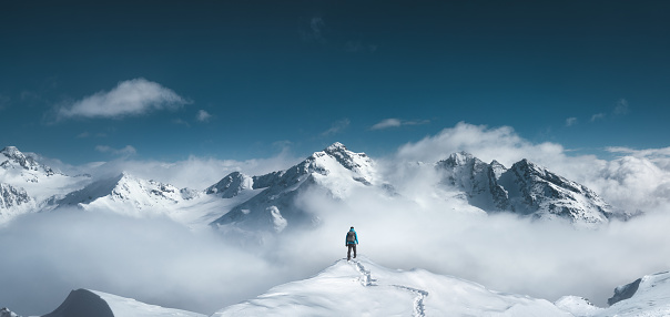 Man standing on the top of a snowcapped mountain peak. Panoramic view.