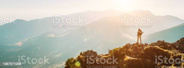 Photo of Mountain hiker with backpack tiny figurine stay on mountain peak with beautiful panorama