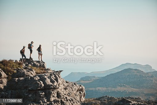 Shot of a group of friends hiking up a mountain
