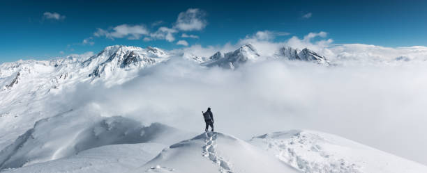 Mountain Hiking Man standing on the top of a snowcapped mountain peak. Panoramic view. mountain stock pictures, royalty-free photos & images