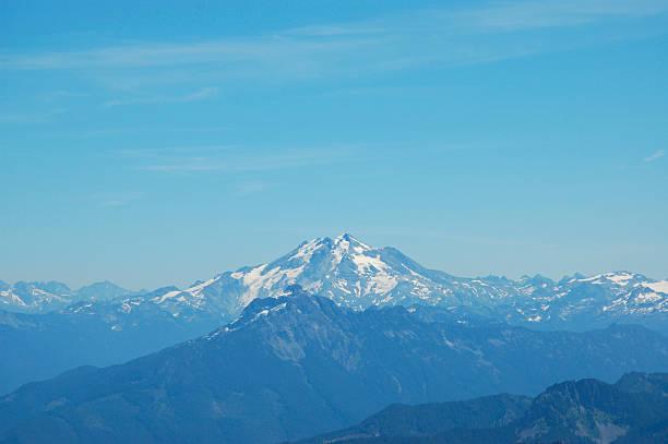 mountain in blue haze against vibrant sky stock photo