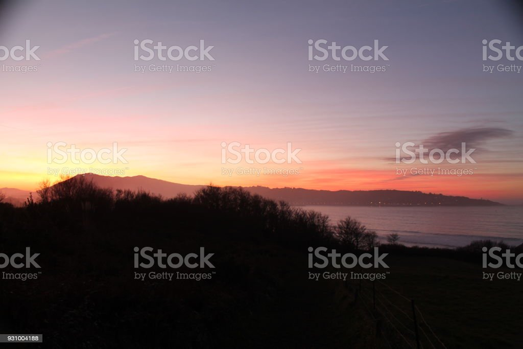 mountain Jaizkibel back lit on atlantic coastline in beautiful pink...