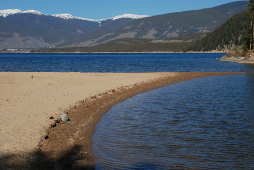 A curved sand spit formed in a mountain lake.
