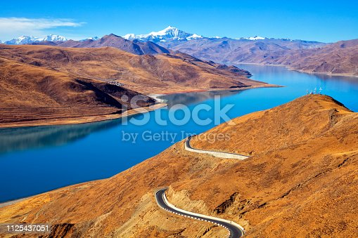 Yamdrok Lake at a height of 4900 m, mountain range and winding road  in Himalaya, Tibet. In the background is seen Noijinkangsang peak (7206 m). Yamdrok Lake is situated about 100 km from Lhasa, the capital of Tibet.
