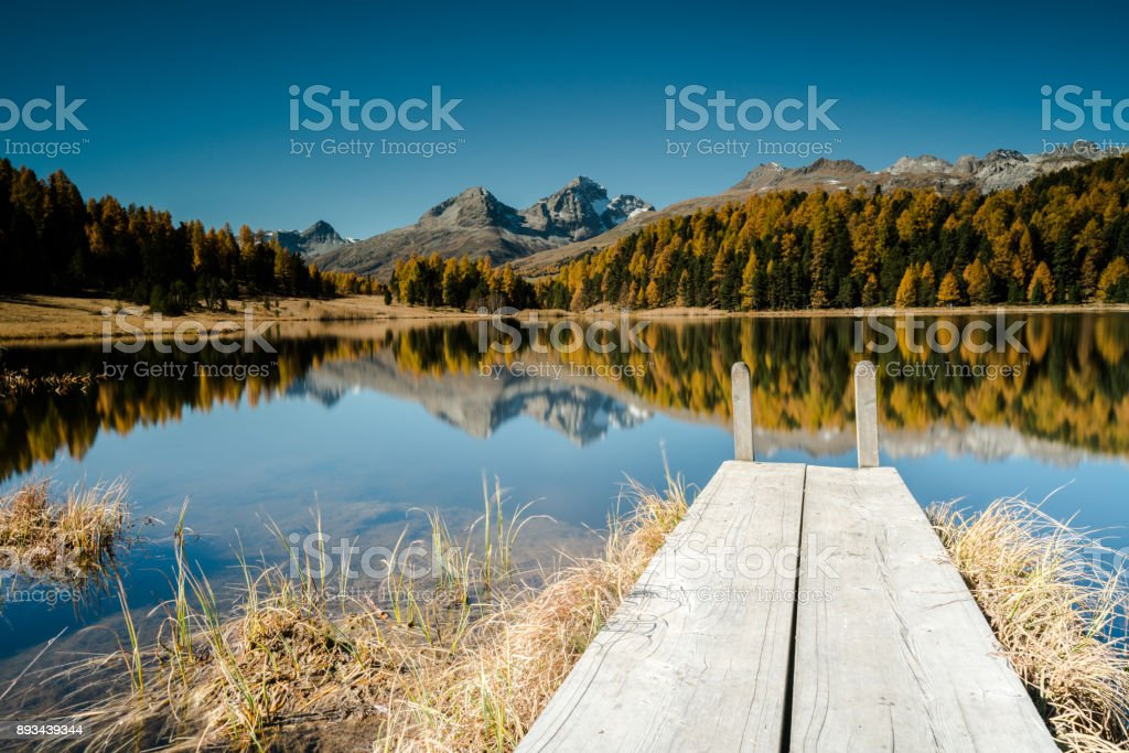 mountain lake in the Swiss Alps near St. Moritz with a wooden pier stock photo