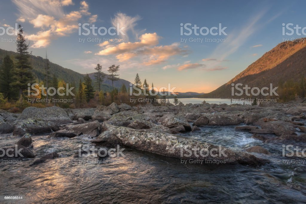 Mountain lake on the background of the morning autumn forest, sunrise royalty-free stock photo